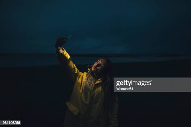 france, brittany, landeda, dunes de sainte-marguerite, woman taking a selfie on the beach at night - gabardina ropa impermeable fotografías e imágenes de stock