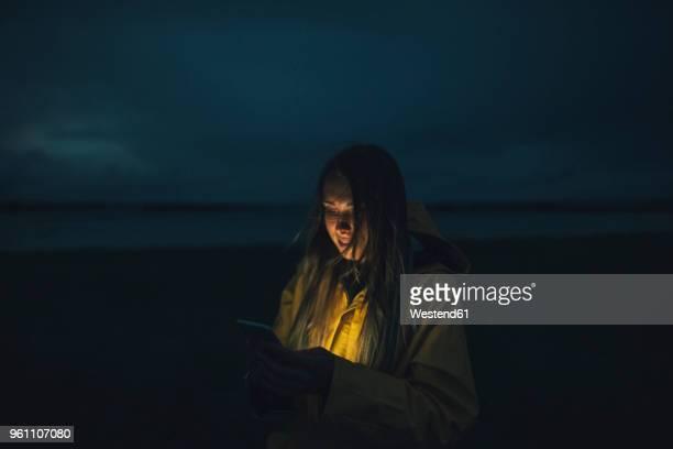 france, brittany, landeda, dunes de sainte-marguerite, woman using cell phone on the beach at night - gabardina ropa impermeable fotografías e imágenes de stock