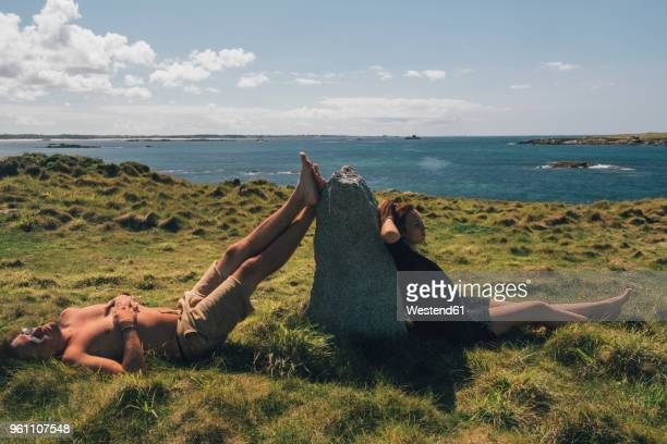 France, Brittany, Landeda, Dunes de Sainte-Marguerite, young couple relaxing in grass at the coast