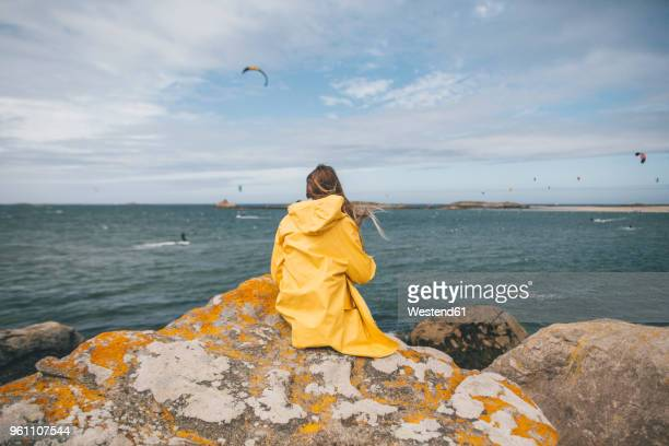 France, Brittany, Landeda, Dunes de Sainte-Marguerite, young woman sitting on rock at the coast
