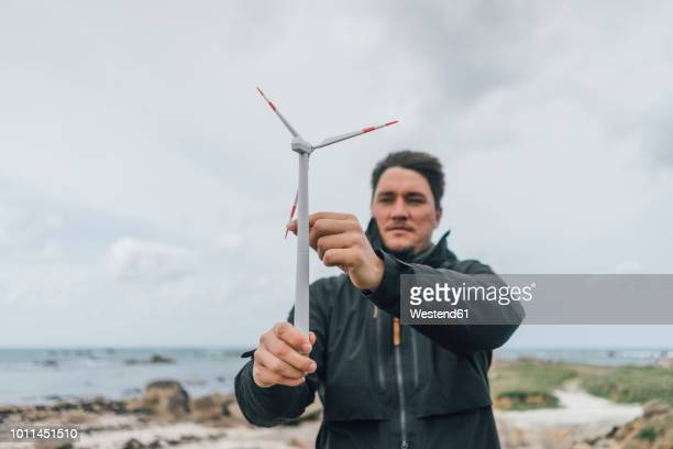 france, brittany, meneham, man with miniature wind turbine at the coast - marine engineering stock pictures, royalty-free photos & images