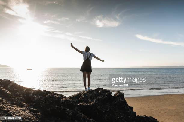 france, brittany, rear view of young woman standing on rock at the beach at sunset - les bras écartés photos et images de collection