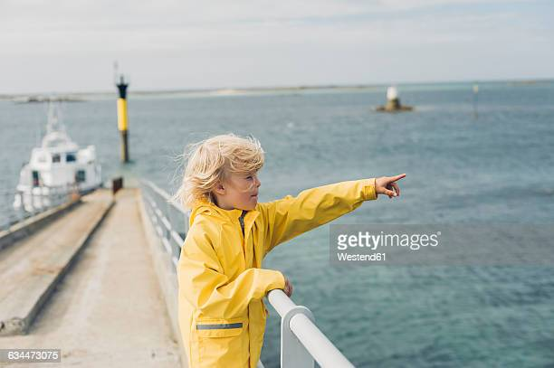 France, Brittany, Roscoff, boy at the harbor pointing his finger