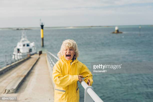 France, Brittany, Roscoff, boy screaming at the harbor
