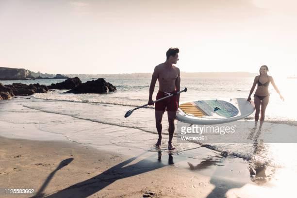 france, brittany, young couple carrying an sup board at the sea together - remo atividade física - fotografias e filmes do acervo