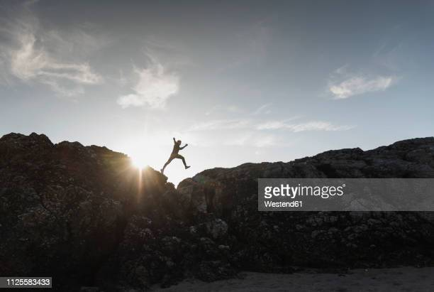 france, brittany, young man jumping on a rock at sunset - outdoor pursuit stock pictures, royalty-free photos & images