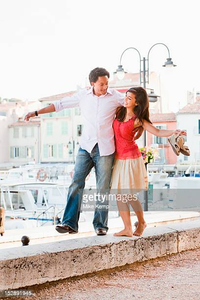 France, Cassis, Couple balancing on stone wall