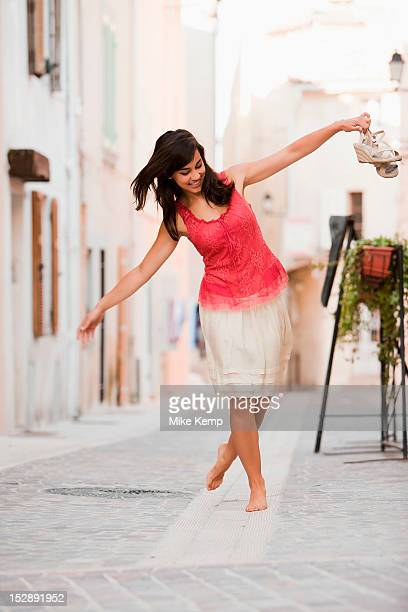 France, Cassis, Young woman balancing on curbstone