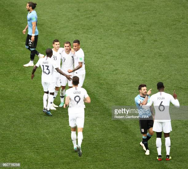 France celebrate their side's second goal scored by Antoine Griezmann while Nahitan Nandez of Uruguay argues with Paul Pogba of France during the...