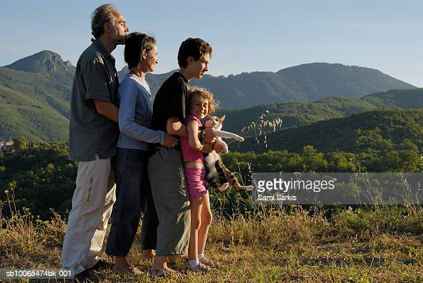 France, Cevenes Mountains, family including two kids (7-13) embracing, side view