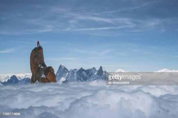 france, chamonix, mont blanc, aguille du midi, climber standing on top of rock in mountains - grandiose photos et images de collection