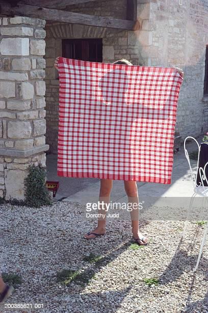 France, Charente, boy (6-8) holding up cloth