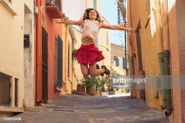 france, collioure, young woman jumping in an alley - 25 29 anos imagens e fotografias de stock