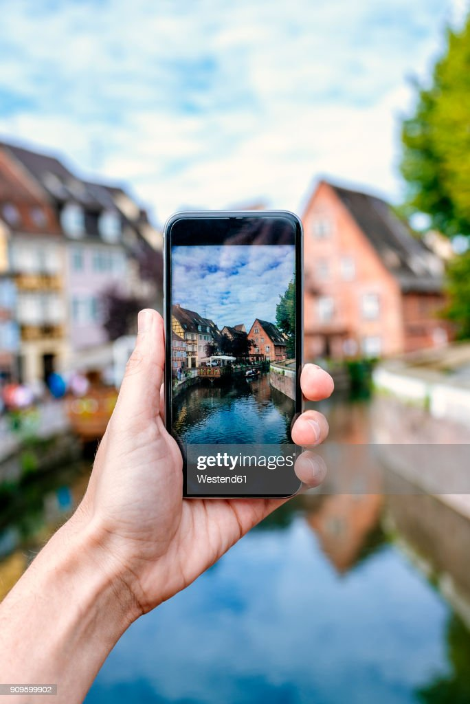 France, Colmar, close-up of a hand of a man taking a picture with his smartphone : Stock Photo