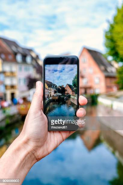 france, colmar, close-up of a hand of a man taking a picture with his smartphone - colmar stock photos and pictures