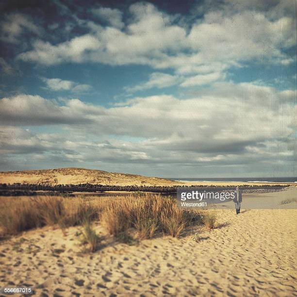 France, Contis-Plage, man walking along the dunes