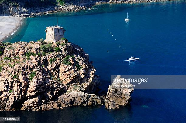 France Corsica Golfe Di Porto Porto Genoese tower on rocky headland with blue waters and boats