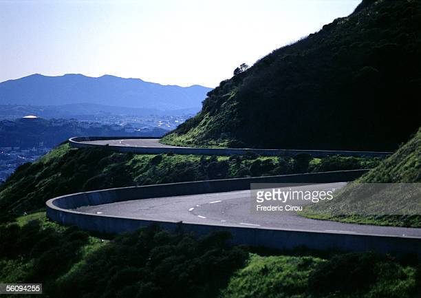 france, corsica, road curving around mountain. - hairpin curve stock photos and pictures
