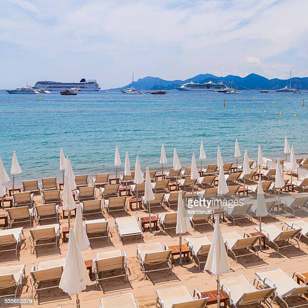 France, Cote d'Azur, Cannes, sun loungers and beach umbrellas on beach