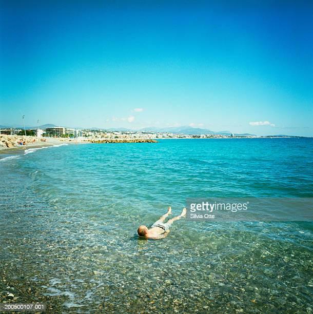 France, Cote d'Azur, Nice, man floating in Mediterranean Sea
