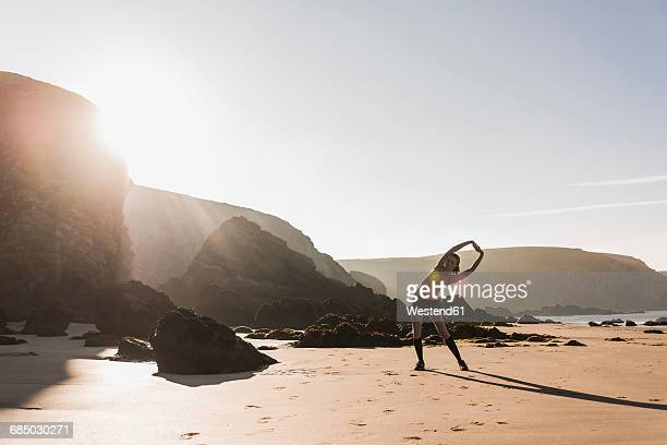 france, crozon peninsula, sportive teenage girl stretching on the beach - warming up stock pictures, royalty-free photos & images