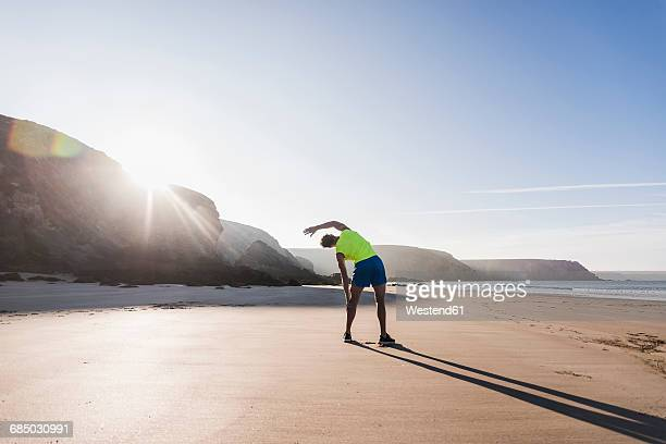 France, Crozon peninsula, sportive young man stretching on the beach