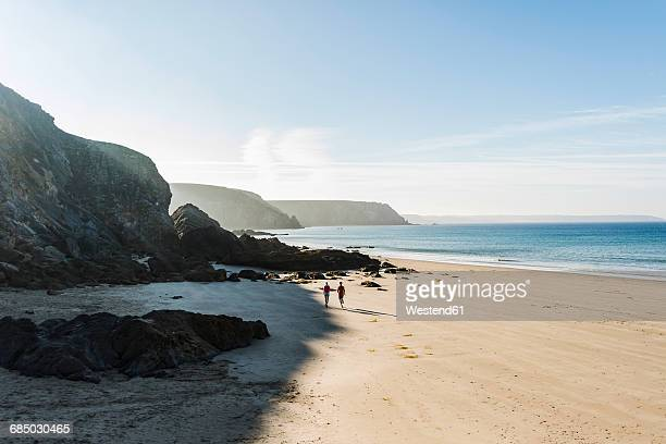 France, Crozon peninsula, young couple running on the beach
