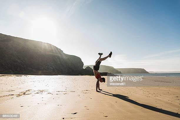 France, Crozon peninsula, young man doing a handstand on the beach
