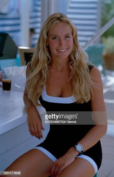 France, Côte d'Azur , juillet 1997 : la mode des maillots de bain sur la plage de Saint-Tropez. Jeune femme blonde , accoudé à un comptoir en maillot...