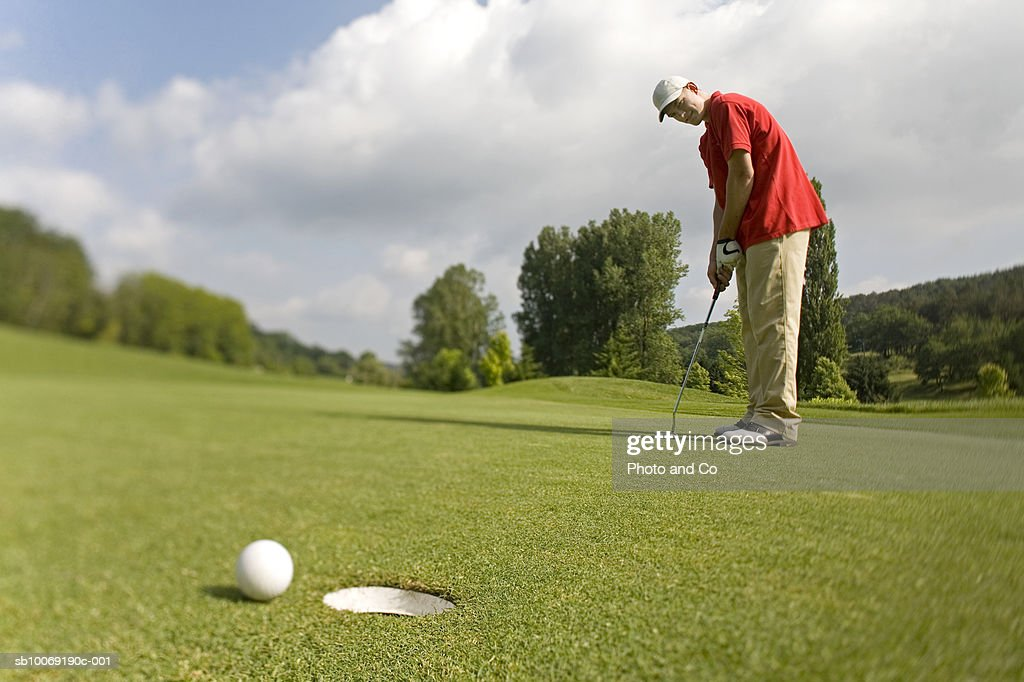 France, Dordogne, golfer putting ball on green : Stockfoto