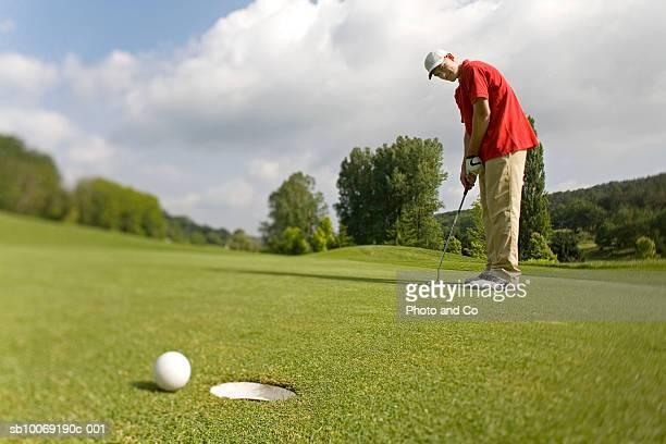 France, Dordogne, golfer putting ball on green