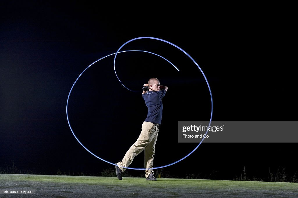 France, Dordogne, golfer swinging club on golf course at night, blurred motion : Stockfoto