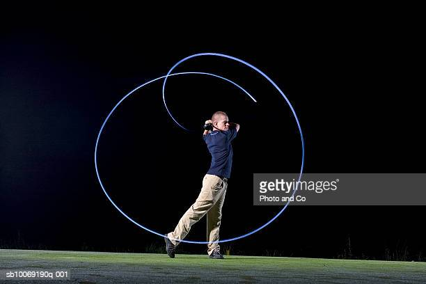 france, dordogne, golfer swinging club on golf course at night, blurred motion - ゴルフのスウィング ストックフォトと画像