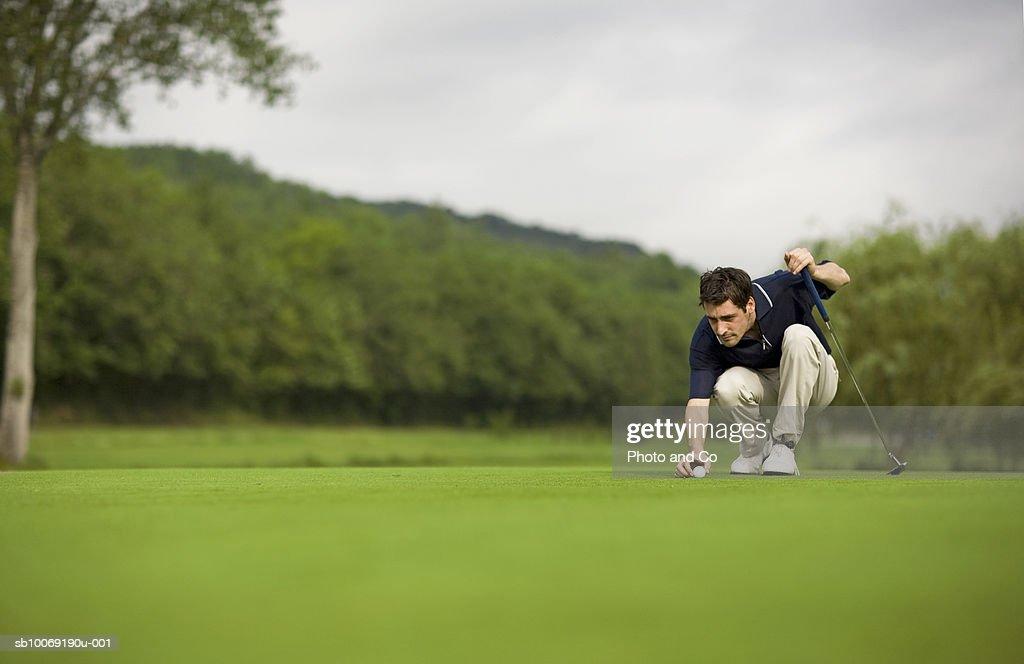 France, Dordogne, male golfer lining up shot on green : Stockfoto
