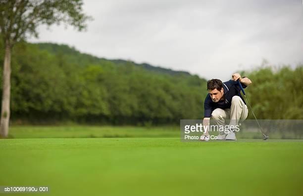 france, dordogne, male golfer lining up shot on green - einlochen golf stock-fotos und bilder