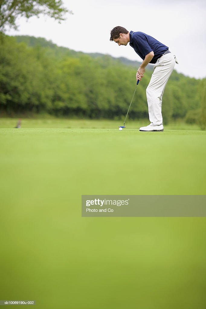 France, Dordogne, male golfer putting ball on green, surface view : Stockfoto