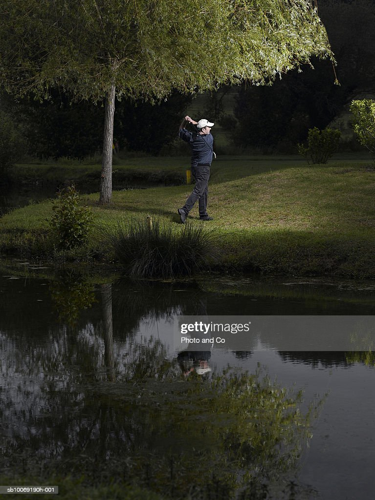 France, Dordogne, male golfer swinging club beside pond on golf course at dusk : Stockfoto