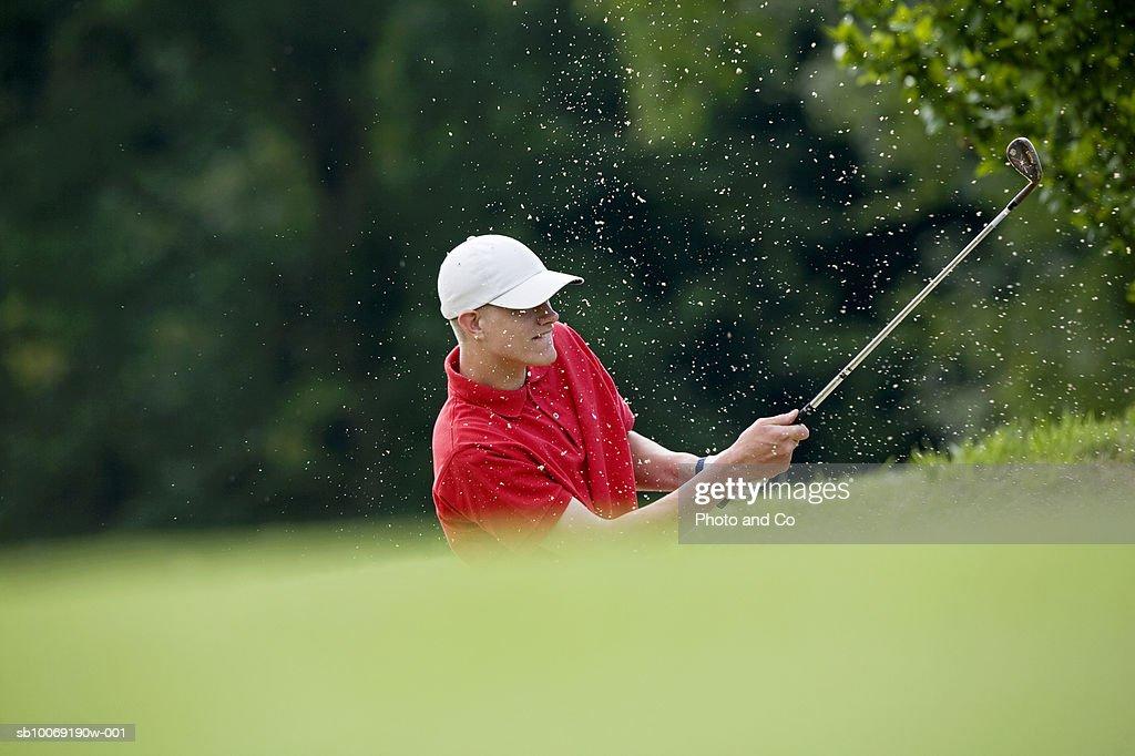 France, Dordogne, male golfer swinging club in bunker on golf course : Stockfoto