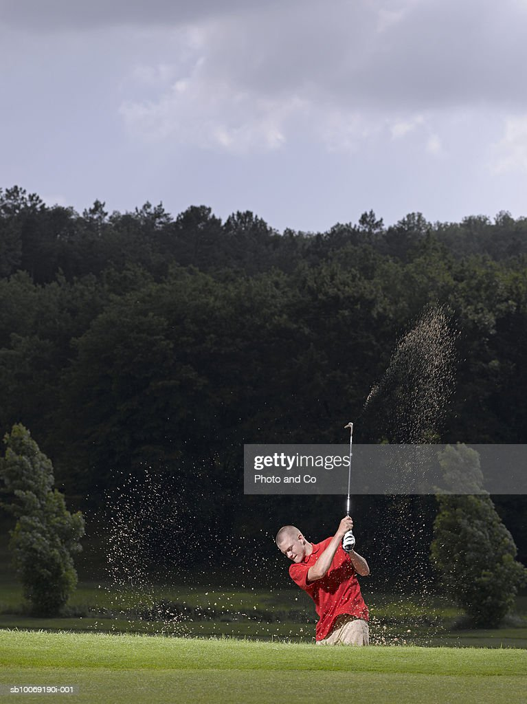 France, Dordogne, male golfer swinging club in sand trap : Stockfoto