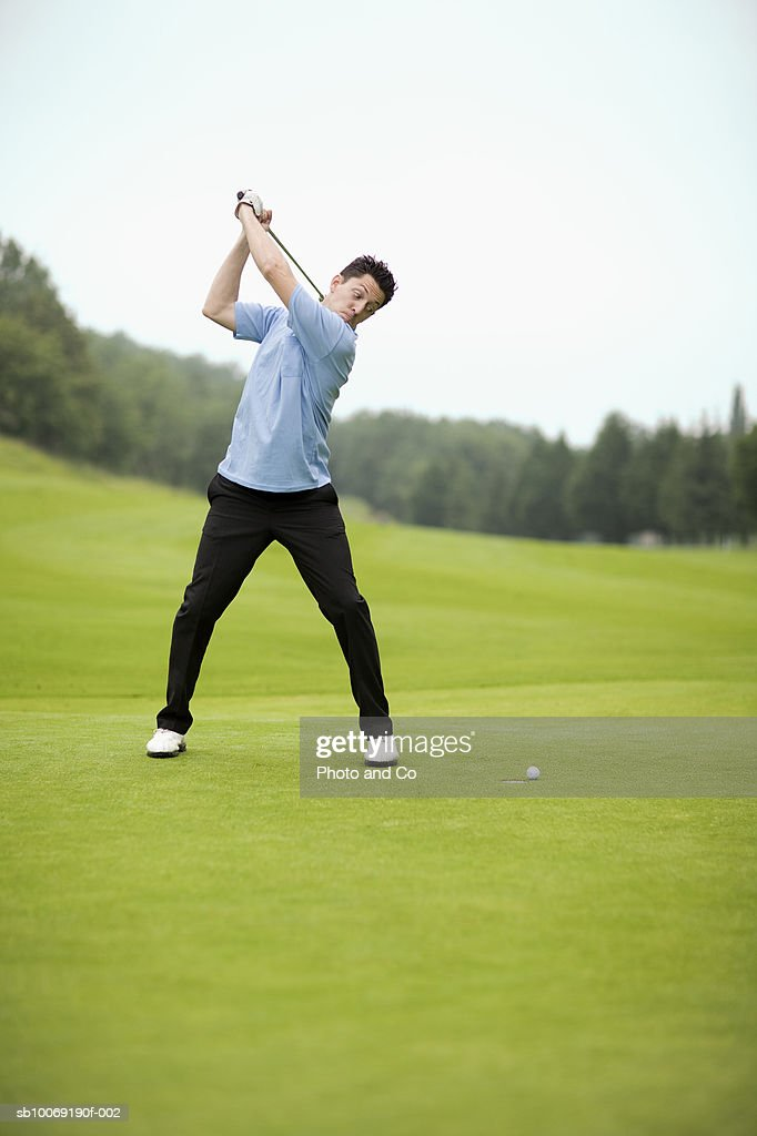 France, Dordogne, male golfer swinging club on golf course : Stockfoto