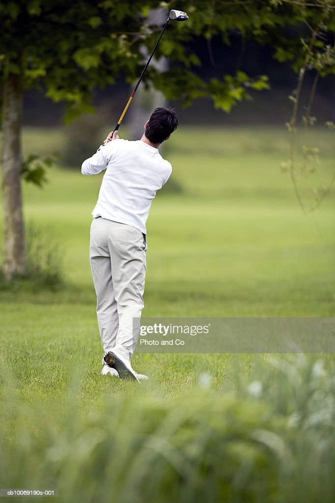 France, Dordogne, male golfer swinging club on golf course, rear view : Stockfoto