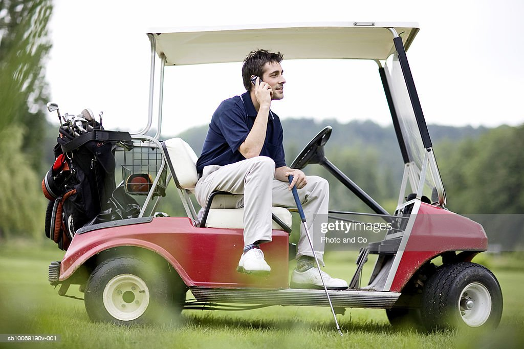 France, Dordogne, male golfer using mobile phone in golf cart : Stockfoto