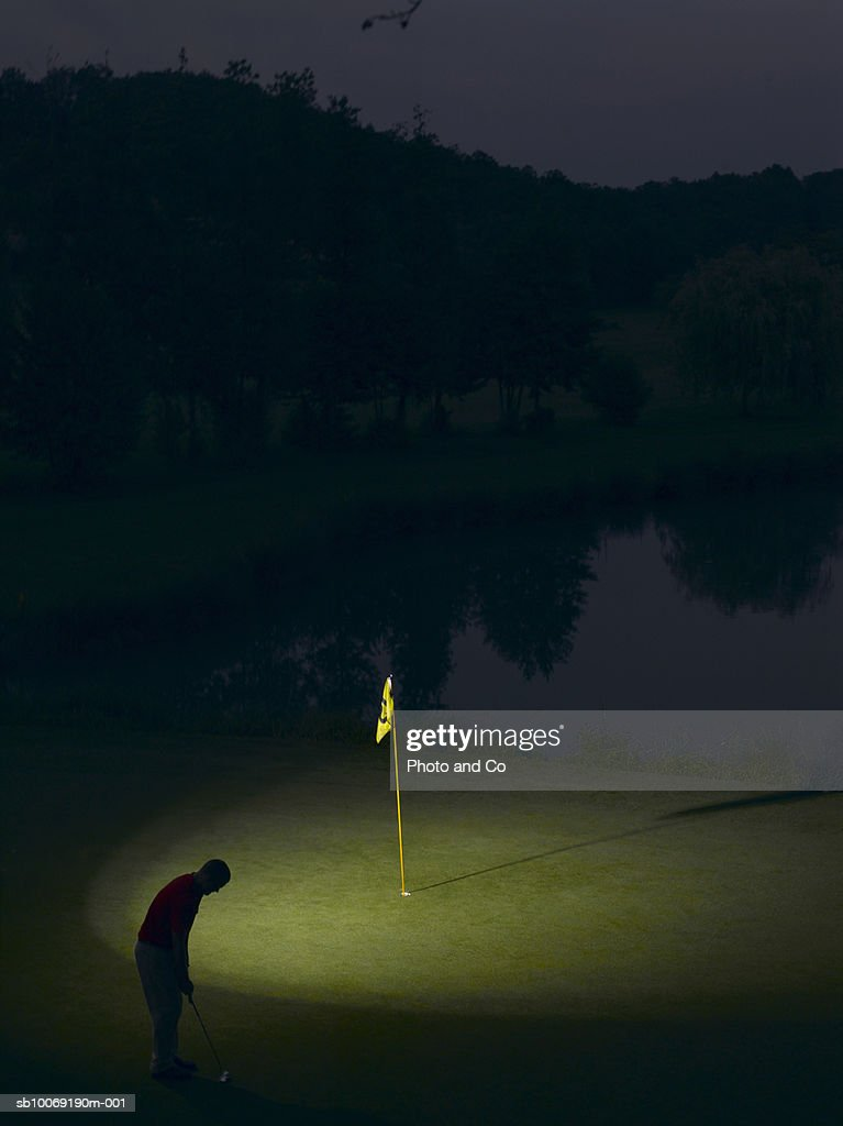 France, Dordogne, silhouette of golfer putting ball on green at night : Stockfoto