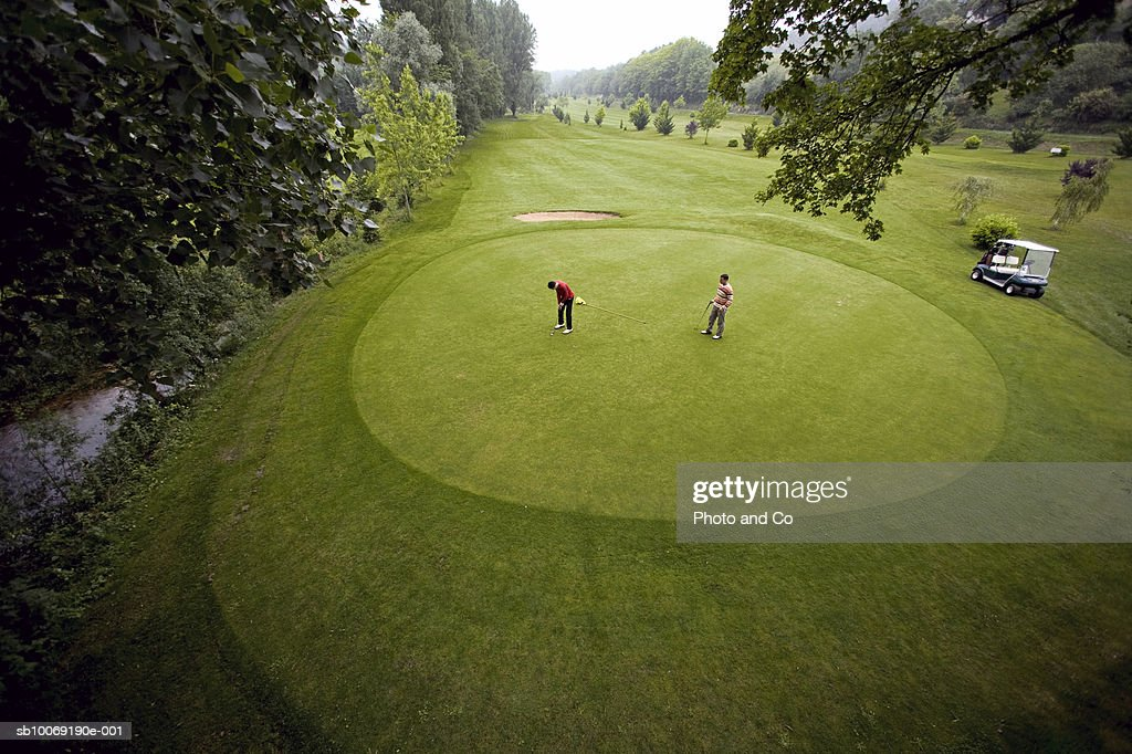 France, Dordogne, two golfers on green at golf course, elevated view : Stockfoto