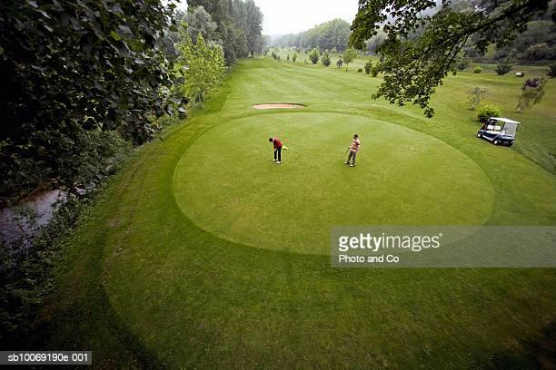 france, dordogne, two golfers on green at golf course, elevated view - green de golfe - fotografias e filmes do acervo