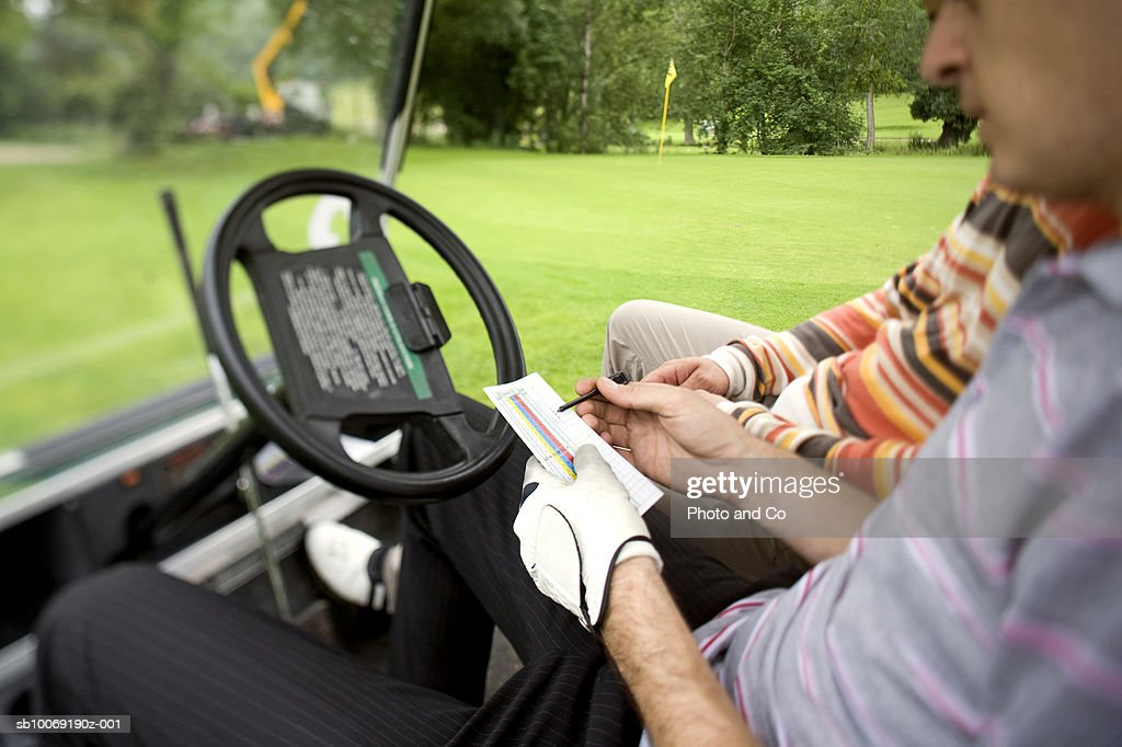 France, Dordogne, two male golfers with score cards in golf cart, close up : Stockfoto