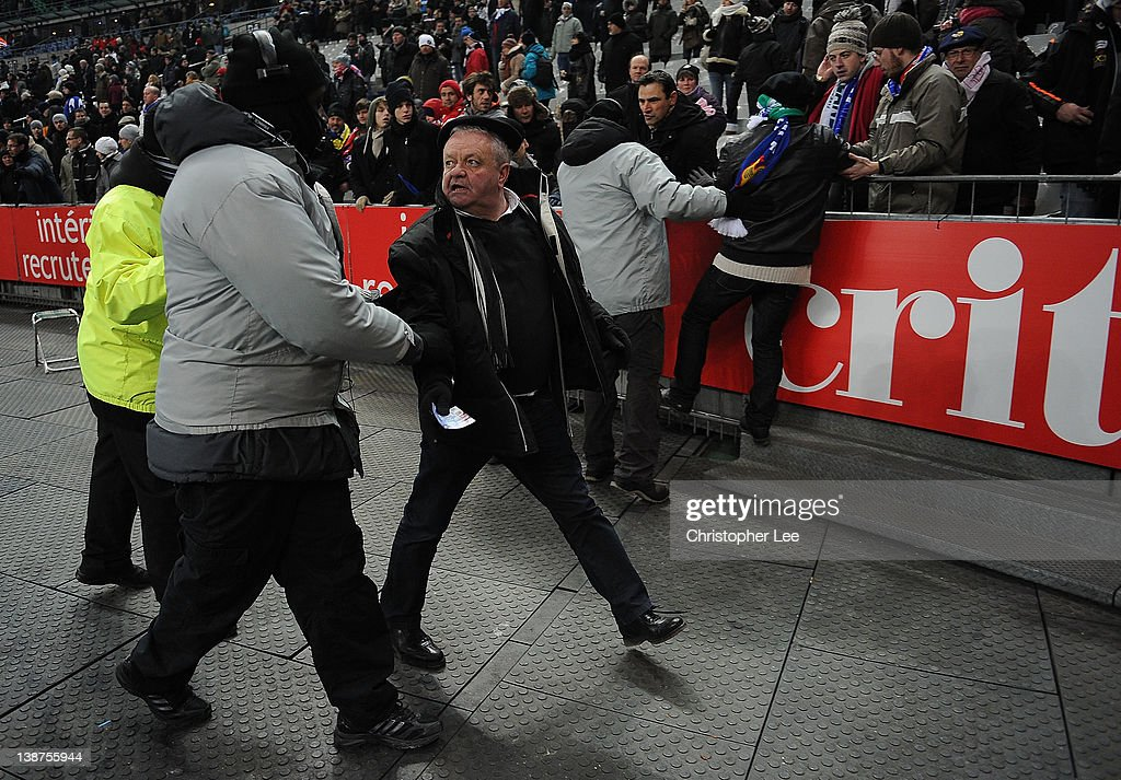 France fans are escorted out the stadium after climbing over the barriers during the RBS 6 Nations match between France and Ireland at Stade de France on February 11, 2012 in Paris, France.