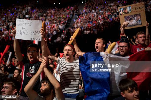 France fans holding baguettes and a flag react as they watch the final of the 'LCS' the first European division of the video game 'League of Legends'...