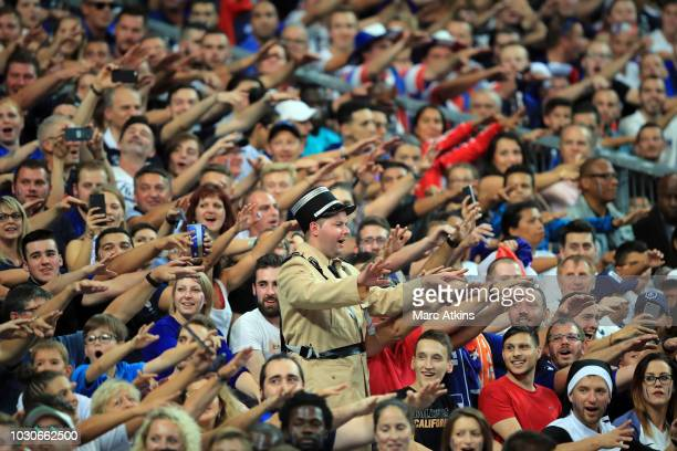 "France fans surround a fellow supporter dressed as a Gendarme from the film ""The Gendarme of Saint-Tropez"" during the UEFA Nations League A group one..."
