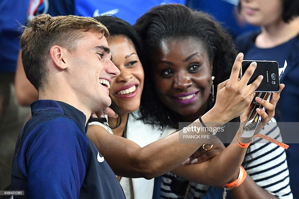 France forward Antoine Griezmann, who scored both goals for France, and fans pose for a photograph as they celebrate their 2-0 win over Germany in the Euro 2016 semi-final football match between Germany and France at the Stade Velodrome in Marseille on July 7, 2016. France will face Portugal in the Euro 2016 finals on July 10, 2016 / AFP / FRANCK